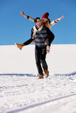 Pares que juegan en nieve Hombre que da paseo del transporte por ferrocarril de la mujer el vacaciones del invierno Imagenes de archivo