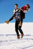 Pares que juegan en nieve Hombre que da paseo del transporte por ferrocarril de la mujer el vacaciones del invierno Fotografía de archivo libre de regalías