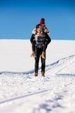 Pares que juegan en nieve Hombre que da paseo del transporte por ferrocarril de la mujer el vacaciones del invierno Fotografía de archivo