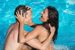 Pares que juegan en piscina Imagen de archivo libre de regalías