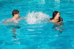 Pares que juegan en piscina Foto de archivo libre de regalías