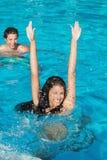 Pares que juegan en piscina Foto de archivo