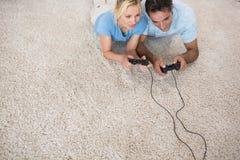 Pares que juegan a los videojuegos en la alfombra Fotografía de archivo