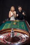 Pares que juegan triunfos de la ruleta en el casino imagen de archivo