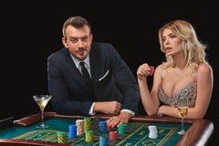 Pares que juegan triunfos de la ruleta en el casino imagenes de archivo