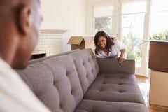 Pares que levam dia movente de Sofa Into New Home On foto de stock royalty free