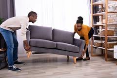 Pares que levantam Sofa In Living Room imagem de stock