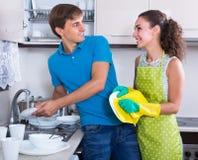 Pares que limpam pratos após o jantar imagem de stock