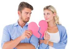 Pares que llevan a cabo dos mitades del corazón quebrado Imágenes de archivo libres de regalías