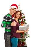 Pares que llevan a cabo el regalo de Navidad Imágenes de archivo libres de regalías