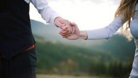 Pares que llevan a cabo las manos que caminan en puesta del sol Romántico en amor en la puesta del sol de la montaña Cierre para  almacen de metraje de vídeo