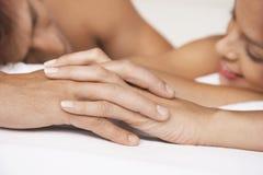 Pares que llevan a cabo las manos en cama Imagen de archivo libre de regalías