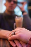 Pares que llevan a cabo las manos en el café Imágenes de archivo libres de regalías