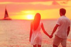 Pares que llevan a cabo las manos juntas en la puesta del sol de la playa fotografía de archivo libre de regalías
