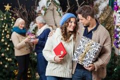 Pares que llevan a cabo regalos de Navidad con los padres adentro Imagen de archivo libre de regalías