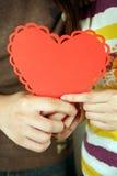 Pares que llevan a cabo un corazón rojo Fotos de archivo libres de regalías