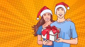 Pares que llevan el hombre y a la mujer de Santa Hats Hold Gift Happy en el concepto de Pin Up Background Winter Holidays del car Imagen de archivo libre de regalías