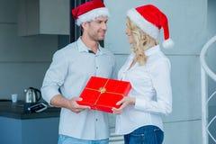 Pares que llevan a Santa Hats Exchanging Gift fotos de archivo