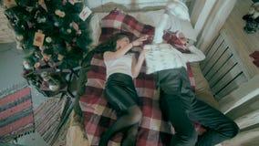 Pares que luchan con el árbol de navidad adornado cercano de las almohadas metrajes