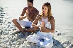 Pares que meditam ao sentar-se na praia fotografia de stock royalty free