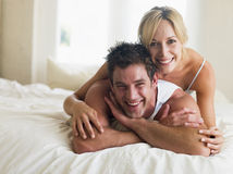 Pares que mienten en la sonrisa de la cama Fotografía de archivo libre de regalías