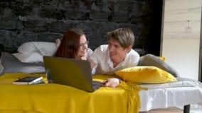 Pares que mienten en la sonrisa feliz del ordenador portátil del uso de la cama que charla en línea, la chica joven y el hombre p almacen de metraje de vídeo