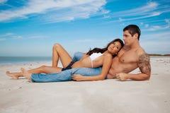 Pares que mienten en una playa Imagenes de archivo