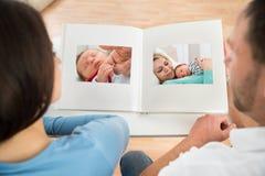 Pares que miran el álbum de la foto del bebé Imagenes de archivo