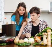 Pares que miran el cuaderno durante cocinar verduras Imagenes de archivo
