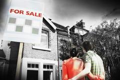 Pares que miran el nuevo hogar con para la muestra de la venta Imágenes de archivo libres de regalías