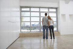 Pares que miran fuera de ventana en el apartamento vacío imágenes de archivo libres de regalías