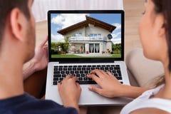 Pares que miran la casa en el ordenador port?til fotografía de archivo libre de regalías