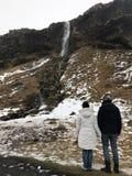 Pares que miran la cascada en Islandia imagen de archivo libre de regalías