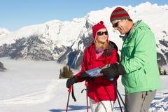 Pares que miran la correspondencia mientras que el día de fiesta del esquí Imágenes de archivo libres de regalías