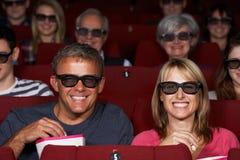 Pares que miran la película 3D en cine Foto de archivo