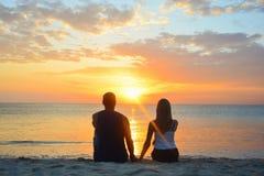 pares que miran la puesta del sol en la playa Fotografía de archivo libre de regalías