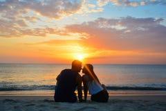pares que miran la puesta del sol en la playa Foto de archivo