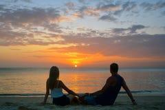 pares que miran la puesta del sol en la playa Imagen de archivo libre de regalías
