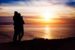 Pares que miran la puesta del sol y el océano Foto de archivo libre de regalías