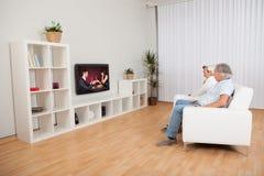Pares que miran la televisión romántica Imagen de archivo libre de regalías
