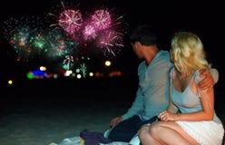 Pares que miran los fuegos artificiales coloridos en la playa Imagen de archivo