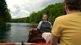 Pares que montam em um barco de enfileiramento no lago video estoque