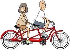 Pares que montam uma bicicleta construída para dois Fotografia de Stock Royalty Free
