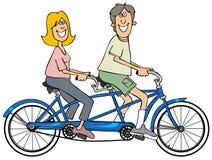 Pares que montam uma bicicleta em tandem azul Fotografia de Stock