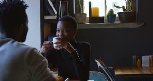 Pares que obran rec?procamente con uno a mientras que comiendo caf? en el caf? 4k almacen de video