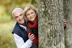 Pares que ocultan detrás de árbol Imagen de archivo libre de regalías