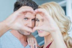 Pares que olham através das mãos que fazem a forma do coração fotos de stock royalty free