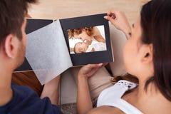 Pares que olham através do álbum de fotografias fotografia de stock royalty free