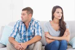 Pares que olham ausentes ao sentar-se no sofá Imagens de Stock Royalty Free