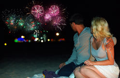Pares que olham fogos-de-artifício coloridos na praia Imagem de Stock